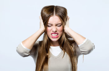 Woman with hearing problemscovering her ears